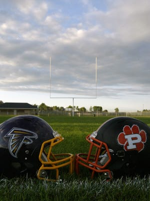 Sheboygan Falls, left, and Plymouth football teams' helmets at Plymouth's football field Tuesday, Aug. 12, 2014. The Sheboygan Falls and Plymouth football teams are determined to keep their long-running rivalry alive after this year, the last time they'll play each other as part of the same Eastern Wisconsin Conference. Plymouth is leaving the conference in 2015.