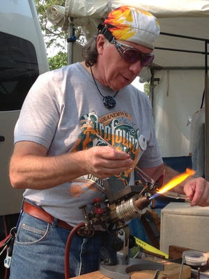 Charlie Shoulders is a skilled glass artist who is making a hummingbird using glass rods which he shapes after warming in the intense heat of the blow torch. It was fascinating for people to watch the progress of his work.
