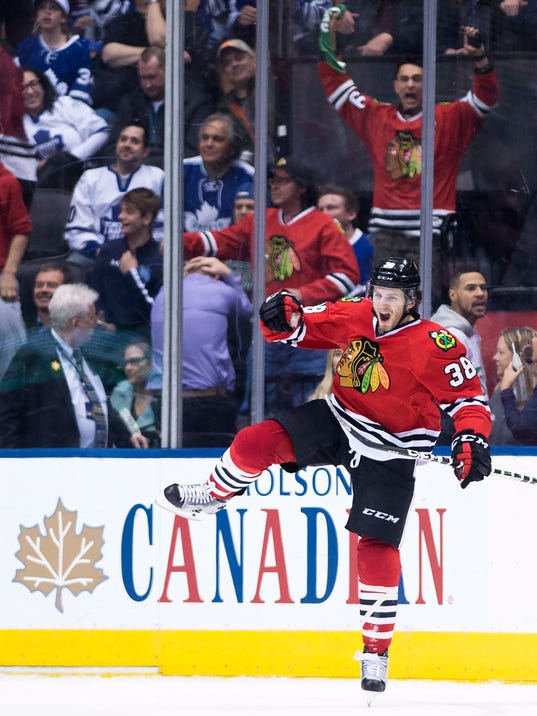 Chicago Blackhawks left wing Ryan Hartman (38) celebrates after scoring the game-winning goal during overtime in an NHL hockey game against the Toronto Maple Leafs, in Toronto on Saturday, March 18, 2017. (Nathan Denette/The Canadian Press via AP)