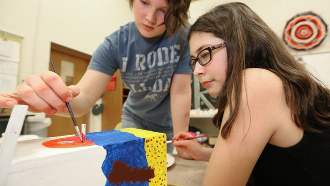 Stangel Elementary School sixth-graders Katie Stockhausen, left, and Rori Beatty, both 11, work on painting their birdhouse Wednesday for a fundraiser auction. The pair decided to design beach theme for their birdhouse.