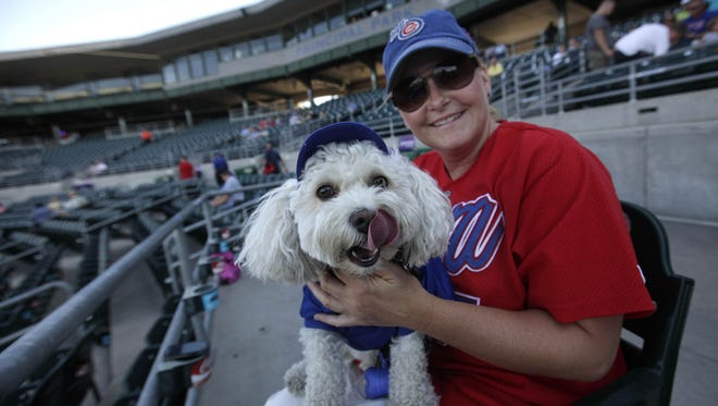 Heather Burnside and her dog Cooper wait for friends to arrive before the parade begins during the Dog Days of Summer at Principal Park Monday evening.