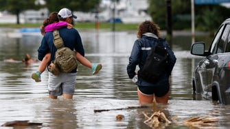 Don Noel carries his daughter Alexis, 8, with his wife Lauren, right as they walk through a flooded roadway to check on their boat in the West End section of New Orleans.