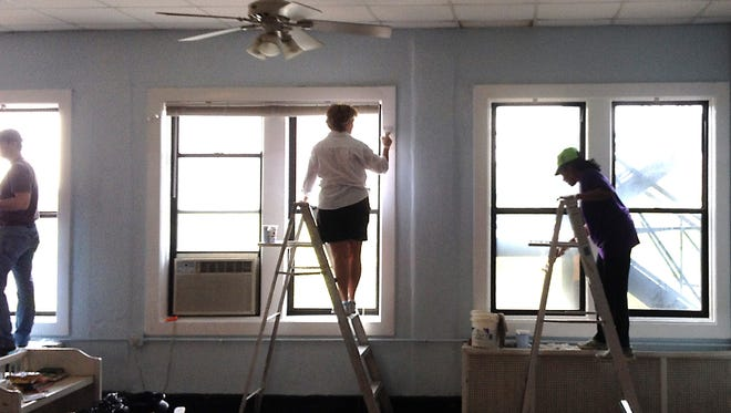 A crew from the Courier-Journal newsroom pitched in to paint a room at the YMCA Chestnut as part of Give-a-Day volunteer program.