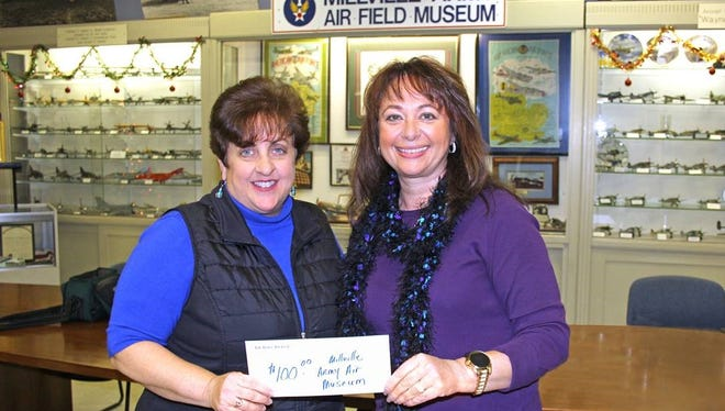Lisa Jester (left), executive director for Millville Army Air Field Museum, accepts a donation of $100 from Robin Adams, advertising manager for The Daily Journal. The donation represents the proceeds of a Wrap for Charity event held on Dec. 9 at Boscov's at the Cumberland Mall in Vineland. Daily Journal representatives Robin Adams, Deborah Marko and Tina Langley wrapped gifts for holiday shoppers who generously gave donations for the museum.