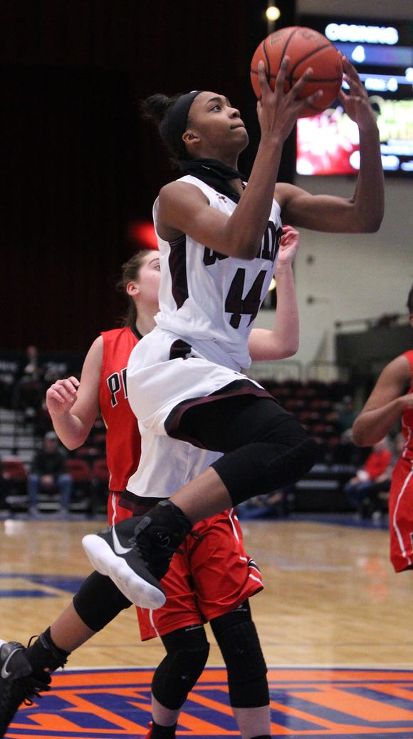 Ossining's Aubrey Griffin drives on Penfield's Baylee