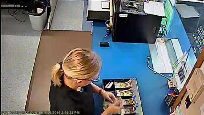 Video surveillance footage shows Melissa Mueller removing cash from a Cudahy Police Department register, according to a criminal complaint charging the department dispatcher with misconduct in office and theft. Credit Milwaukee County District Attorney's Office.