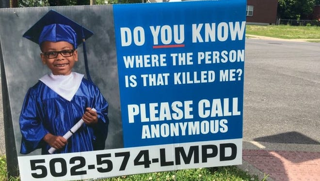 A sign asking for information about Dequante Hobbs Jr.'s murder.