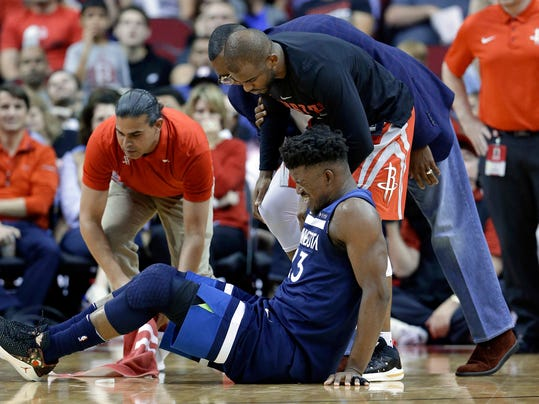 Minnesota Timberwolves guard Jimmy Butler (23) reacts to a knee injury on the court as Houston Rockets guard Chris Paul (3) and team trainers hover over him during the second half of an NBA basketball game Friday, Feb. 23, 2018, in Houston. (AP Photo/Michael Wyke)