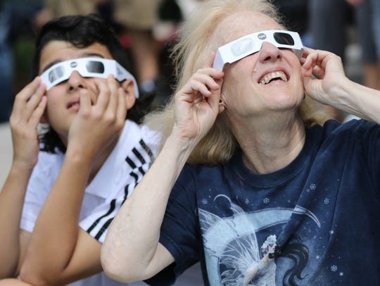 Eileen White and Ziad Souki, 12, watch the solar eclipse