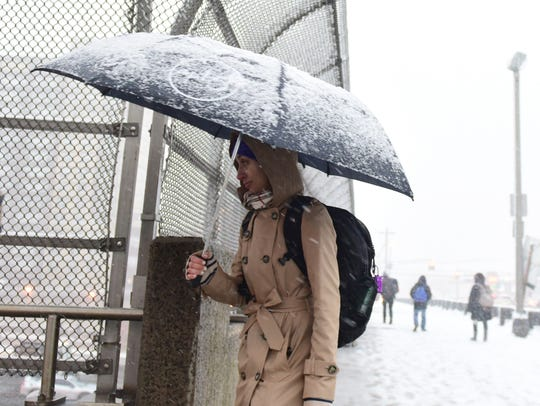 A commuter makes her way in the snow to the bus stop
