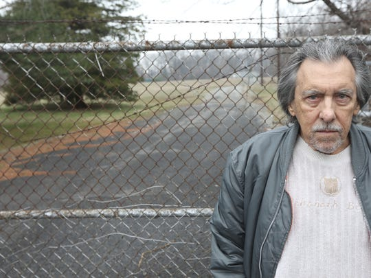 Ron Vuyosevich, 71, poses in front of a gate near Christopher Columbus Highway
