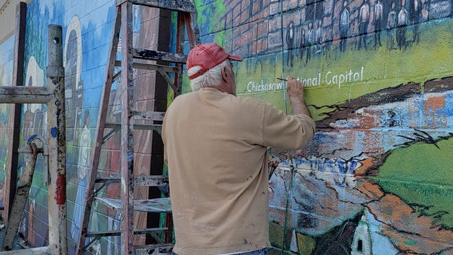 Bob Palmer puts the finishing touches on the city's latest mural Monday afternoon. The mural is composed of five panels with each panel depicting a portion of the Chickasaw Nation and its people.