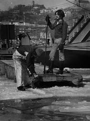 February 1977: Unidentified men break up ice in the frozen Ohio River in Cincinnati, Ohio.