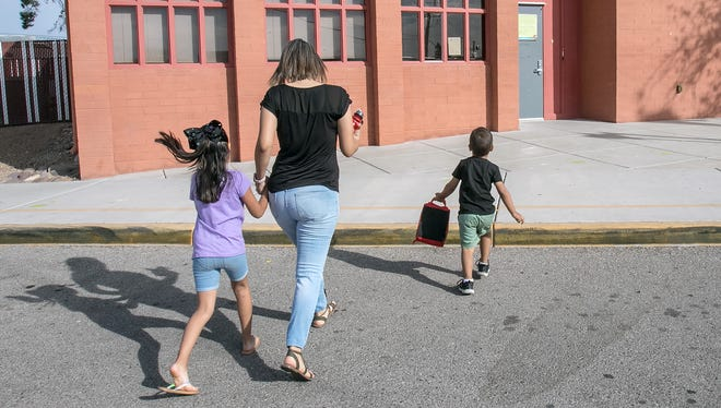 Diana Tapia drops off her son Alec, 3, to the day care at Walker Early Learning Center on the campus of Walker Elementary School which is open during the teacher walkout on April 26, 2018 in Tucson, AZ. Tapia said she would take her daughter Anail, 7, left, a Walker Elementary student with her to work.