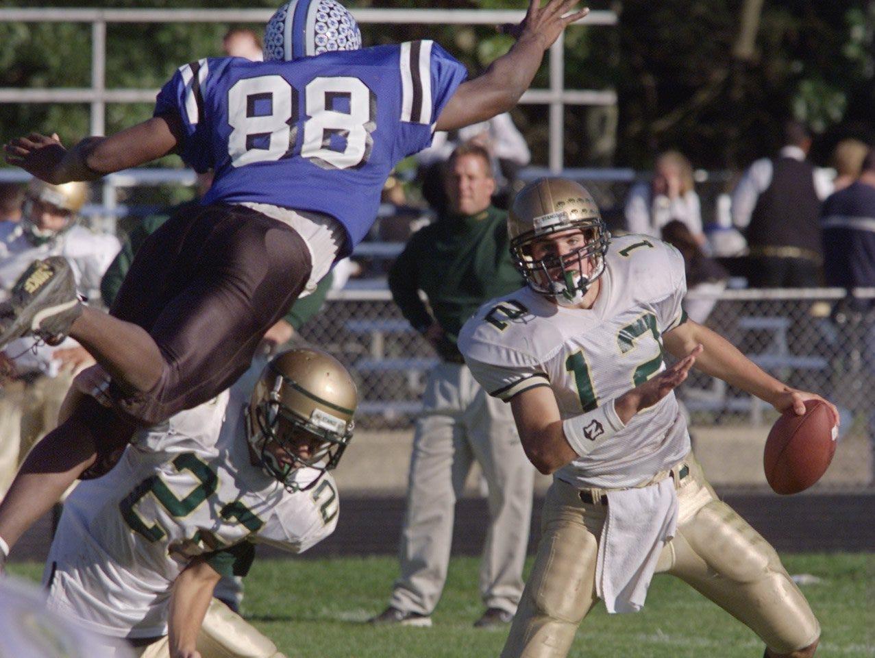 Lakewood's Thomas Carroll (88) dives at Brick Memorial quarterback Brian Boland (12) in a 2001 game.
