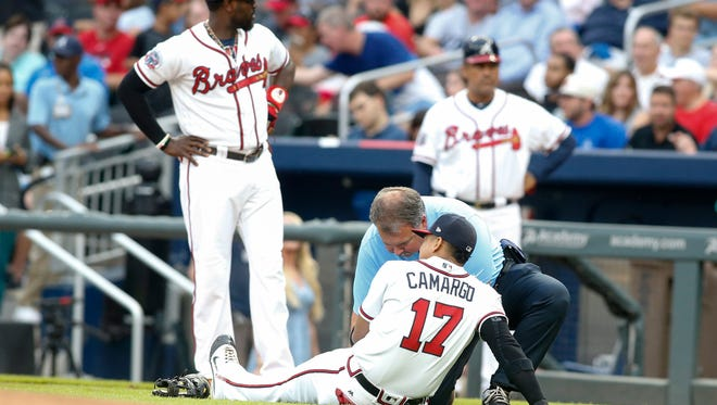 Braves shortstop Johan Camargo is examined by trainer Jim Lovell after being injured.