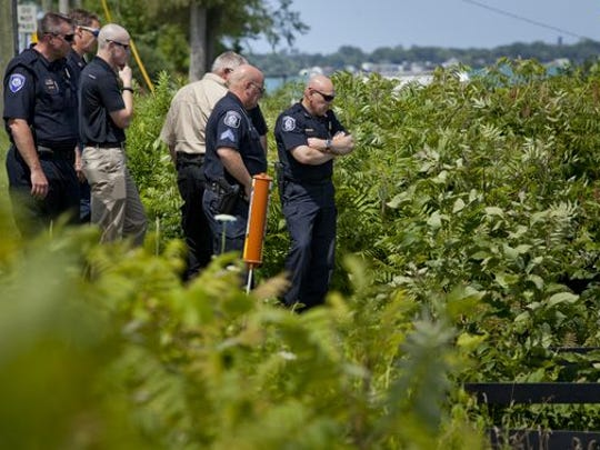 Marysville Police, Fire and members of the St. Clair County Sheriff's Department work the scene where a body was found in the St. Clair River Thursday, July 16, 2015, in the 1300 block of River Road in Marysville.