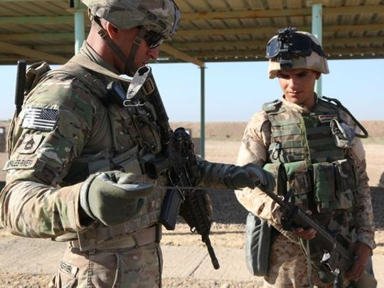 Sgt. 1st Class Rapherson Morales-Rivera, a paratrooper assigned to 3rd Brigade Combat Team, 82nd Airborne Division, clears an Iraqi soldier's weapon at Camp Taji, Iraq, on June 21.