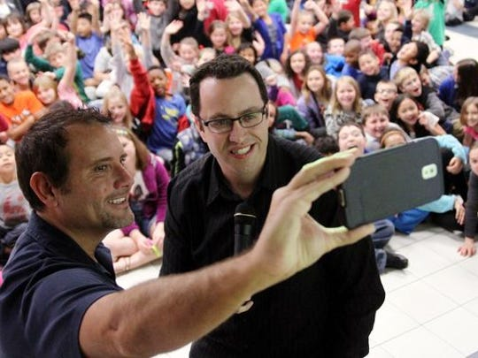 """Russ Taylor, former executive director of the Jared Foundation, left, and Jared Fogle, """"the Subway guy,"""" pose to take a selfie with the students of Euper Lane Elementary School in Ft. Smith, Ark., on March 20, 2014, after speaking to the children about the dangers of childhood obesity."""