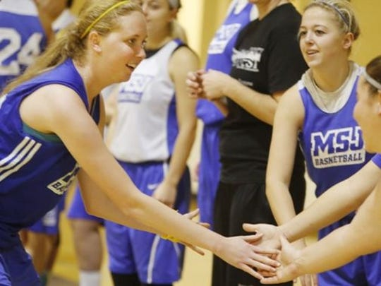 Mt. St. Joseph College freshman basketball player Lauren Hill is congratulated by teammates after making a lay-up in practice.