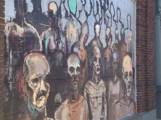 """Sagan Newham's """"Walking Men"""" graced a wall of Haywood Printing at Fifth and Ferry streets before it was painted over."""