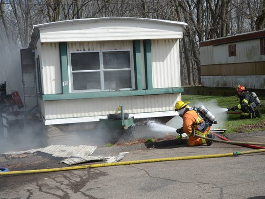 Firefighters spray water under the mobile home as the