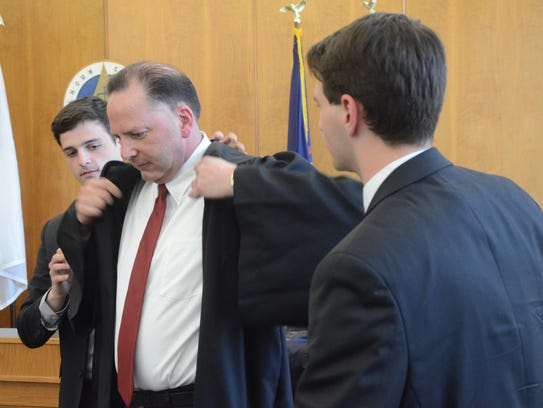 Paul Beardslee is helped with his robe by sons, Nick,