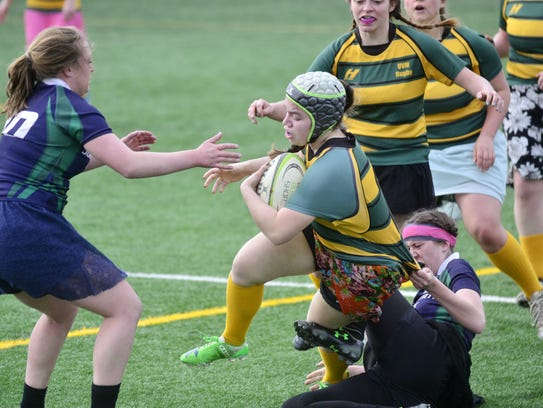 A Johnson State College rugby player tugs on the back