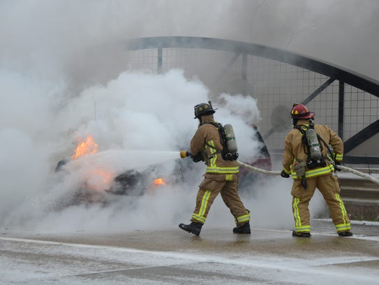 Firefighters extinguish the vehicle fire in the northbound
