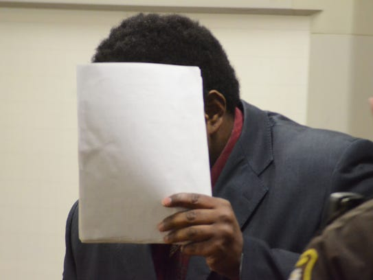 Devree Garner holds papers to avoid a photographer