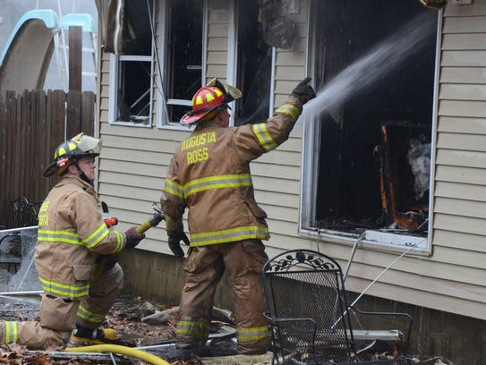 Firefighters work outside a small portion of the house