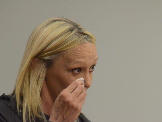 Foster parent Michelle Woodard wipes away tears as