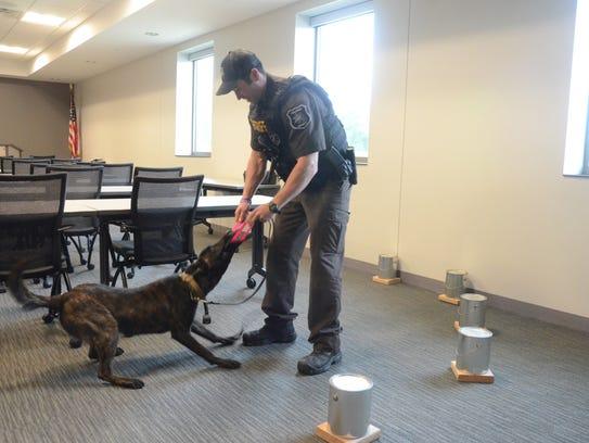 Deputy Matt Burpee plays with Rocket after a training