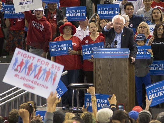 Sen. Bernie Sanders points out a supporter's sign calling