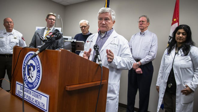 Board of Health President Dr. Brian Miller, center, discusses an order from the Sangamon County Department of Public Health that limits the amount of people at events to 250 or less for the next 30 days to mitigate the spread of coronavirus during a press conference with county officials at the Sangamon County Health Department on March 12 in Springfield.