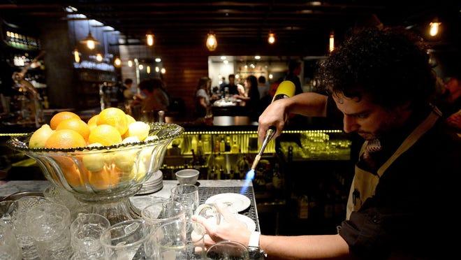 Raffi Jergerian uses a torch to smoke ingredients at underground bar Social.