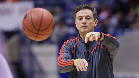 U of L head coach Rick Pitino tosses a basketball into play during a March 27 practice before the Cardinals' Sweet 16 game against Kentucky.