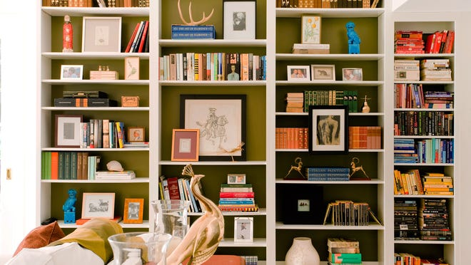 Framed art is displayed both in and on a built-in bookcase. The effect is open and airy, while still providing ample storage space for the homeowner's book collection. The interior and bookcase design is by Molly Luetkemeyer.
