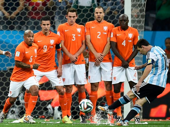 Argentina's Lionel Messi, right, takes a free kick near Netherlands players, from left, Nigel de Jong, Robin van Persie, Stefan de Vrij, Ron Vlaar and Bruno Martins during the semifinal match Wednesdasy.