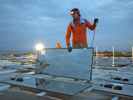 Charlie Quezada installs solar panels at the Palm Springs