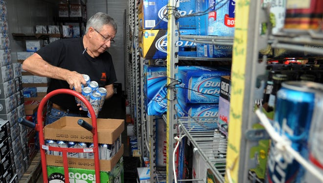 Tom Trutschel stocks shelves in the cooler Thursday at the Ameristop convenience store he owns at the corner of University Drive and Western Avenue.