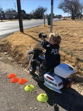 Jordan Petrella, age 4, uses an electric megaphone wrapped in black tape while pretending to be a patrol officer with the San Angelo Police Department