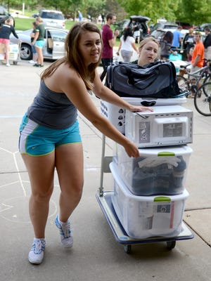 University of Wisconsin-Green Bay student ambassadors Morgen Clarey, left, and Emily Carroll, help freshman students move belongings into Roy E. Downham Hall on Thursday.
