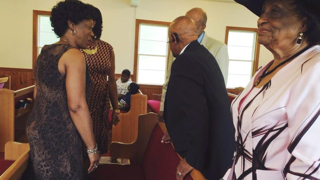 Salem Christian Methodist Episcopal Church congregation members greet one another. Callie Jenkins stands on the far right.