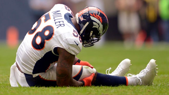Von Miller grabs his knee against the Houston Texans Sunday. He tore his left ACL and will miss the remainder of the season.
