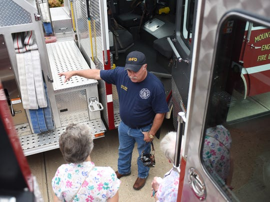 Ken Williams informs visitors about the fire department's equipment during an open house.