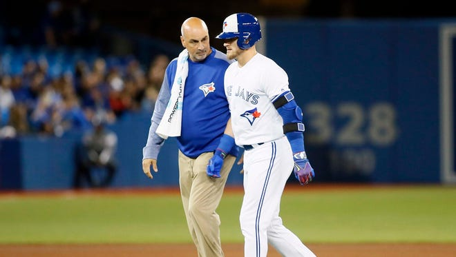 Toronto Blue Jays designated hitter Josh Donaldson walks off the field with trainer George Poulis after hitting an rbi double in the sixth inning against the Baltimore Orioles at Rogers Centre.