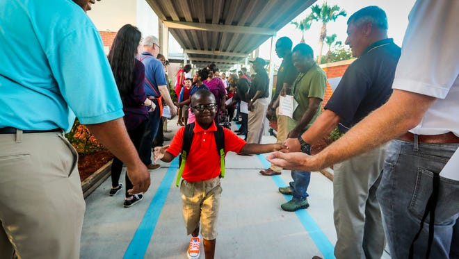 Kaleb Holloway, 5, shakes hands as he walks into  kindergarten for his first day of school and received A Gentlemen's Welcome at Franklin Park Magnet School in Fort Myers. This annual tradition invites male role models and community members to welcome students to school. They line the sidewalks, high-five the kids getting off the buses or walked to school and cheer for the students.
