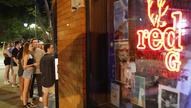 People wait in line to get into a bar in downtown Athens, Ga, on Friday, June 5, 2020.