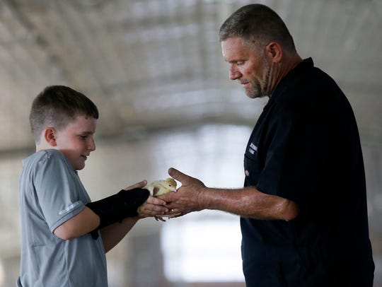 Beau Smotherman, left, hands a baby turkey to his father